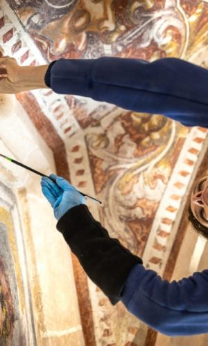 Low Angle View of Female Restorer Working on Paintings in Antique Catholic Church